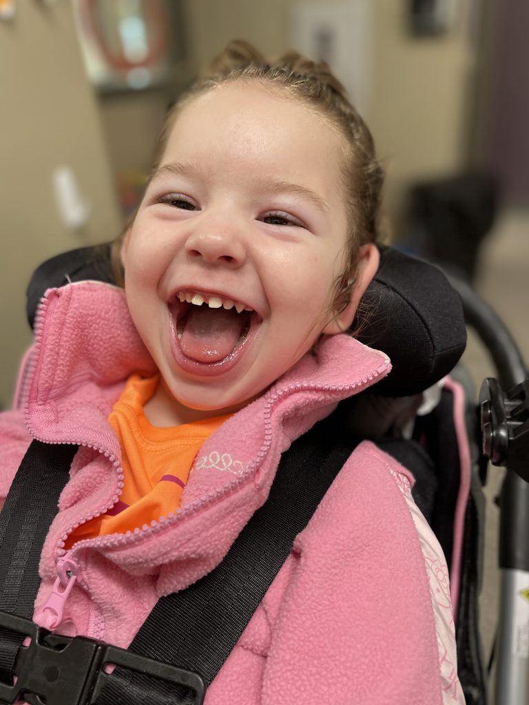 Little girl in a wheelchair with a big smile