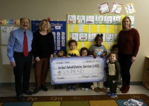 Vitangeli Dental donating a big check to the preschool room